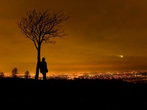 1449634-2-silhouette-of-man-stood-by-tree-overlooking-manchester-city-centre-at-night